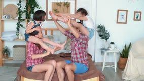 As filhas sentam-se em ombros de seus pais e a família tem o divertimento, movimento lento vídeos de arquivo