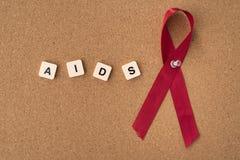 As fitas vermelhas ajudam à fita com palavra de AIDS/HIV no quadro de mensagens imagens de stock royalty free