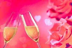 As flautas de Champagne com bolhas douradas em rosas florescem o fundo Fotografia de Stock Royalty Free