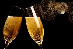 As flautas de Champagne com bolhas douradas fazem elogios com faísca dos fogos-de-artifício e fundo preto Fotografia de Stock Royalty Free