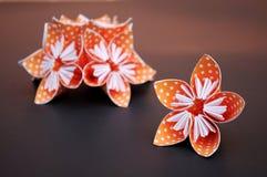 As flores alaranjadas do origâmi feitas da polca pontilharam o papel Fotografia de Stock