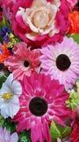 As flores artificiais decoraram a parede Imagem de Stock