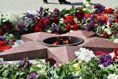 As flores colocadas a uma chama eterno em honra de Victory Day o 9 de maio Imagens de Stock