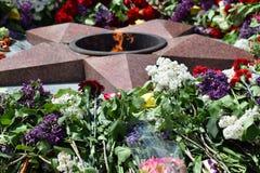 As flores colocadas a uma chama eterno em honra de Victory Day o 9 de maio Foto de Stock