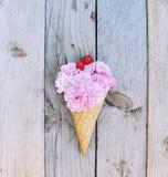 As flores cor-de-rosa das rosas cobriram com cerejas vermelhas no cone de gelado no fundo de madeira rústico Fotografia de Stock