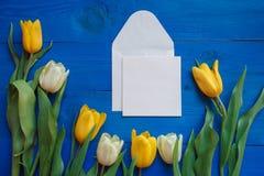 As flores da tulipa da mola e o cartão de papel na tabela de madeira azul de cima no plano colocam o estilo Fotografia de Stock