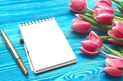 As flores da tulipa e a almofada de nota vazia forram a página no fundo de madeira com espaço da cópia conceito do dia da mulher  Imagens de Stock