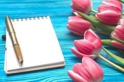 As flores da tulipa e a almofada de nota vazia forram a página no fundo de madeira com espaço da cópia conceito do dia da mulher  Imagens de Stock Royalty Free