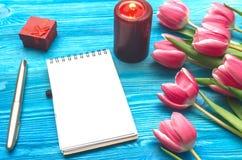 As flores da tulipa e a almofada de nota vazia forram a página no fundo de madeira com espaço da cópia conceito do dia da mulher  Fotos de Stock Royalty Free