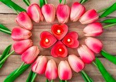 As flores da tulipa são apresentadas na forma de um coração em um fundo de madeira, entre eles são iluminadas velas na forma de u ilustração royalty free