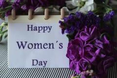 As flores de Liliums e de Helichrysum enviaram sobre o dia das mulheres Mensagem do dia das mulheres felizes no caderno Fotos de Stock Royalty Free