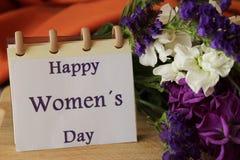 As flores de Liliums e de Helichrysum enviaram sobre o dia das mulheres Mensagem do dia das mulheres felizes no caderno Imagens de Stock Royalty Free