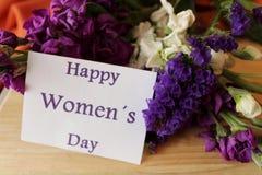 As flores de Liliums e de Helichrysum enviaram sobre o dia das mulheres Mensagem do dia das mulheres felizes no caderno Imagem de Stock