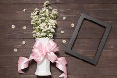 As flores e a moldura para retrato brancas do cortador estão no vaso com a fita no fundo de madeira Foto de Stock