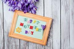 As flores e o quadro bonitos dos açafrões com letras de madeira coloridas soletraram o dia feliz do ` s da mãe em placas de madei Fotografia de Stock Royalty Free