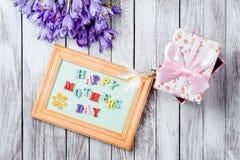 As flores e o quadro bonitos dos açafrões com letras de madeira coloridas soletraram o dia feliz do ` s da mãe em placas de madei Fotos de Stock