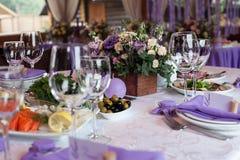 As flores e os vidros de vinho vazios ajustaram-se no restaurante Imagem de Stock