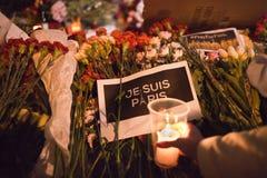 As flores e a vela iluminam-se para vítimas terroristic dos ataques em Paris Imagem de Stock