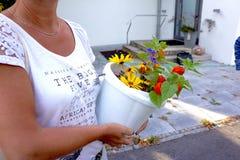 As flores em uma cubeta guardaram por uma mulher Fotos de Stock Royalty Free