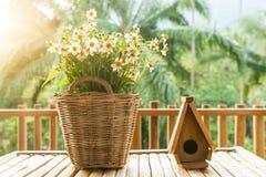As flores na cesta e no pássaro pequeno abrigam feito da madeira em um bambu Foto de Stock