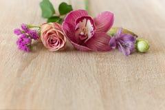 As flores picam gotas da água em uma luz de madeira Fotos de Stock
