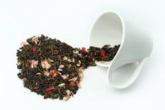 As folhas de chá derramaram um copo virado no fundo branco imagens de stock royalty free