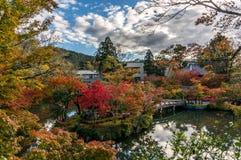 AS FOLHAS de OUTONO COLORIDAS TEMPERAM, cores da folha do outono com o santuário da bordadura da reflexão da skyline e ponte da p Imagens de Stock