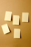 As folhas de papel em branco furaram ao marrom da parede Fotografia de Stock