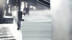 As folhas de papel impressas são servidas na máquina impressora Offset, CMYK imagem de stock