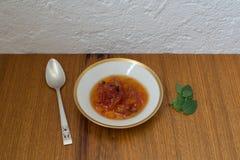 As folhas indianas da manjericão do cravo-da-índia da sobremesa da papaia serviram em pratos de porcelana chineses com colher de  imagem de stock royalty free