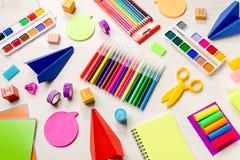 As fontes de escola apresentam com artigos de papelaria coloridos Marcadores, lápis da cor, cadernos na mesa de madeira, vista su imagem de stock