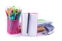 As fontes de escola que incluem um vidro com lápis coloridos registram cadernos um caderno do caderno do furo com uma pena no bac foto de stock