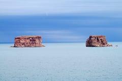 As formações de rocha vermelhas no lago azul molham fotografia de stock
