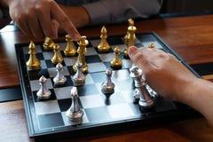 As fotos do close-up das m?os do checkmate em um tabuleiro de xadrez durante um jogo de xadrez o conceito da estrat?gia da vit?ri imagens de stock royalty free