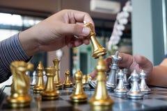 As fotos do close-up das m?os do checkmate em um tabuleiro de xadrez durante um jogo de xadrez o conceito da estrat?gia da vit?ri fotos de stock