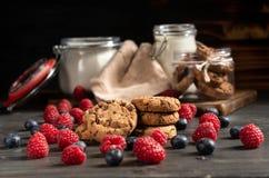As framboesas, os mirtilos e as cookies no foco, no leite e na farinha selaram frascos no fundo fotografia de stock
