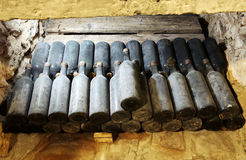 As garrafas antigas do vinho na adega antiga O vi original foto de stock