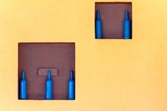 As garrafas azuis em um quadrado arquivam em uma parede amarela Fotos de Stock