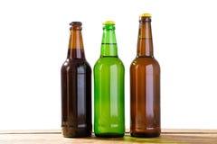 As garrafas de vidro da cerveja diferente no espaço branco claro da cópia do fundo, garrafas diferentes zombam acima foto de stock royalty free