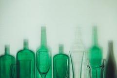 As garrafas de vidro verdes e os vidros de cerveja vazios estão no conceito da bebida da fileira Fotografia de Stock