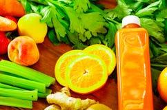 As garrafas do suco orgânico delicioso que encontra-se na mesa sorrounded por frutos e por vegetarianos, cores bonitas, estilo de foto de stock royalty free