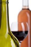 As garrafas e o vidro derramaram com vinho tinto no branco Fotos de Stock