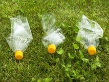 As garrafas plásticas encontram-se na grama verde Polui??o da natureza Desperdícios no gramado imagem de stock