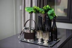 As garrafas pretas do champanhe estão em uma tabela ao lado dos pratos para o gelo e os tenazes de brasa no fundo fotografia de stock