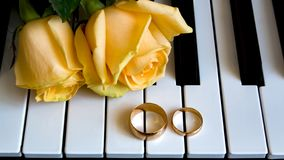 As a gift to the beloved woman, yellow roses lie on the piano with Engagement ring on the wedding day, engagement, international royalty free stock photos