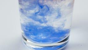 As gotas azuis da pintura da aquarela dissolvem-se na água no vidro vídeos de arquivo
