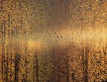 As gotas douradas na janela após a chuva à vista da cidade da noite iluminam-se Fotos de Stock