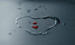 As gotas e o coração da água vermelha dão forma no fundo escuro, foco macio Fotografia de Stock Royalty Free