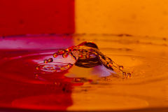 As gotas, pulverizam, espirram da água em um fundo colorido Fotografia de Stock Royalty Free