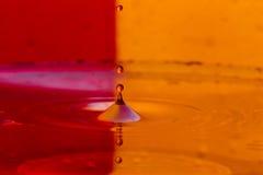 As gotas, pulverizam, espirram da água em um fundo colorido Foto de Stock
